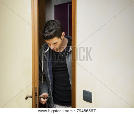 Handsome young man opening door to enter