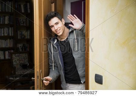 Smiling young man in doorway waving at the camera