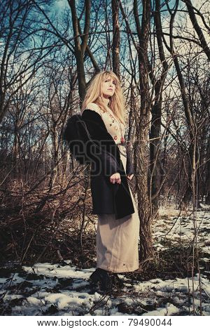 blonde woman in coat and long wool dress stand in the forest, cold winter day, full body shot
