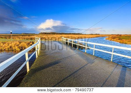 Bridge Over River In A Rural Landscape Lit By Morning Sun