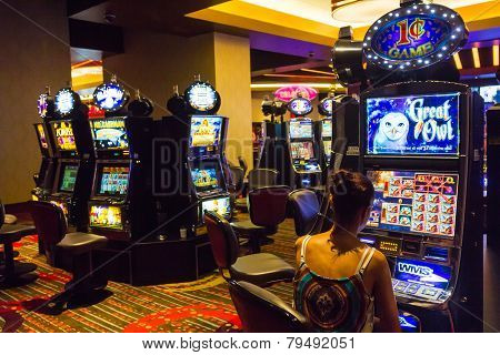 Woman Having Fun Playing At Slot Machines
