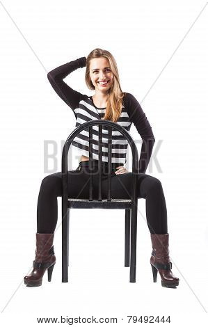 Relaxed Woman Sitting On A Chair Is Smiling