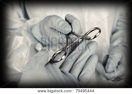 Surgeon's hands holding medical instrument closeup
