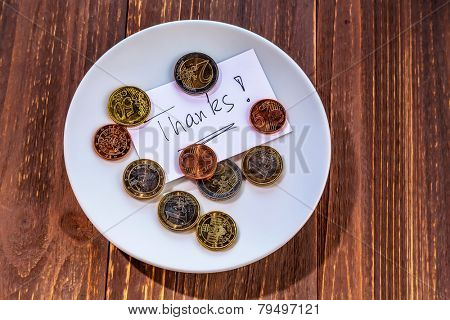 a plate of coins for tips or fee for toilets. in english