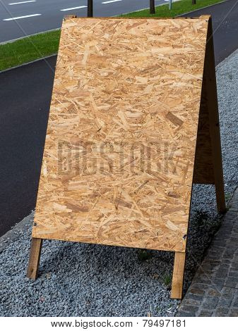 an empty poster stands made of pressed wood shavings. copy space and background