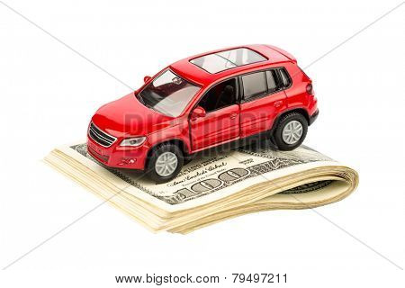 a car is on dollar bills. costs for the purchase of automobiles, gasoline, insurance and other car costs