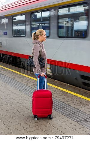 a young woman waiting for a train at a railway station. train ride on vacation
