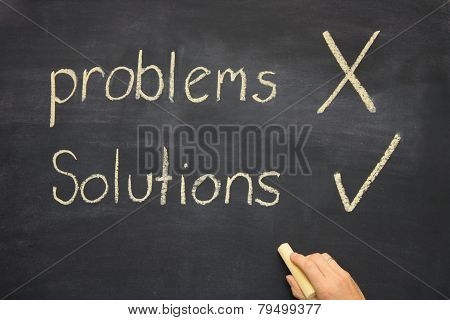 Hand Ticking The Word Solutions On A Blackboard