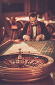 pic of roulette table  - Man in suit and scarf playing roulette in a casino - JPG