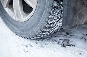 pic of stud  - Fragment of automotive wheel with studded tires and winter snowy road - JPG
