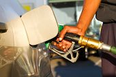 stock photo of high-octane  - a male african pumping gas into car at fuel station - JPG