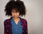 picture of wacky  - Portrait of a beautiful mixed race girl with wacky afro hair style in a checkered shirt isolated against a grey background - JPG