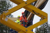 picture of purlin  - Builders use a scissor lift to reach the roof of a building under construction - JPG