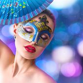 stock photo of incognito  - Beautiful young woman in mysterious venetian carnival blue mask in front of night city illumination - JPG