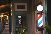 picture of barber  - A Glowing Barber Pole on a Barbershop Porch at Night - JPG