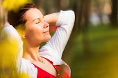 picture of beatitudes  - Portrait of a young beautiful woman with eyes closed smiling in a sunny spring day - JPG