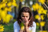 stock photo of sneezing  - Woman with a flu or an allergy is sneezing while standing outside in a park - JPG