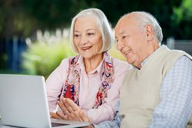 stock photo of chat  - Senior couple video chatting on laptop while sitting at nursing home porch - JPG