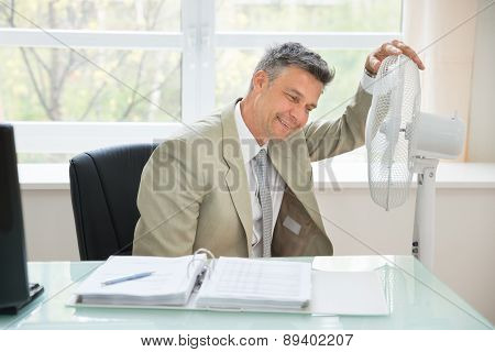 Mid-adult Businessman Sitting Near Fan