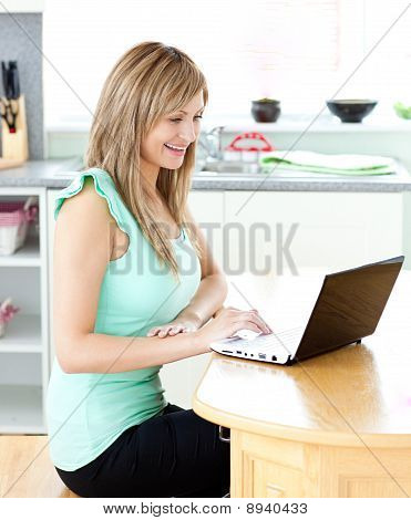 Delighted Blond Woman Using Her Laptop Smiling At The Camera At Home