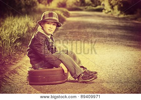 Portrait of a cute dreamy boy sitting on the old suitcase outdoor. Summer day. Adventure.