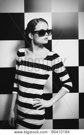 Beautiful fashion model posing in dress in black and white stripes on a background of black and white squares. Beauty, fashion concept. Black-and-white photo.
