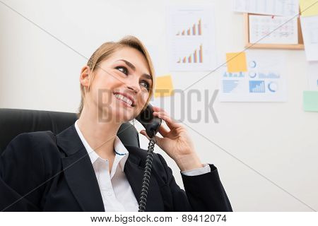Happy Businesswoman Using Telephone