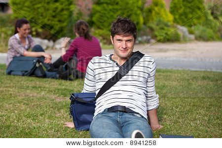 Good-looking Male Student Lying On The Grass With His Schoolbag