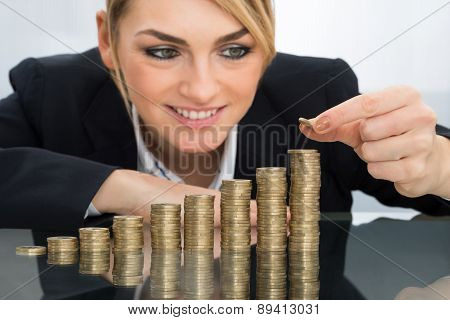 Businesswoman Putting Coin On Stack Of Coins