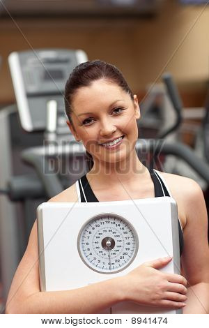 Cute Woman Holding A Scales And Smiling At The Camera