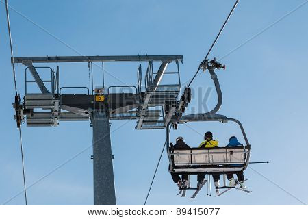 Skiers On Chairlift In Mountain