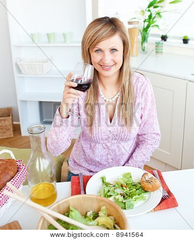 Bright Young Woman Drinking Wine And Eating A Salad In The Kitchen