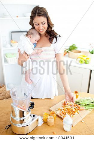 Caring Young Mother Preparing Vegetables For Her Baby In The Kitchen