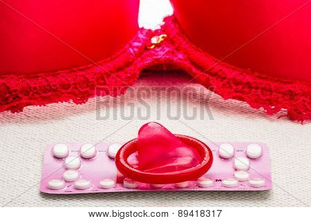 Pills And Condom With Red Bra