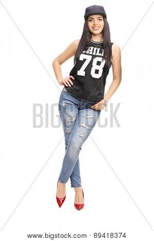 Full length portrait of a young fashionable woman in hip-hop outfit, leaning against a wall isolated on white background