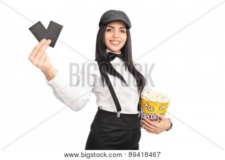 Cheerful female movie director holding a box of popcorn and two tickets isolated on white background