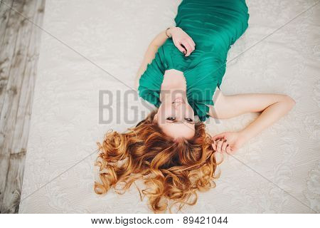 redhead girl with long hair in green dress lying on the bed