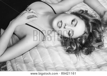 sexy girl with curly short hair lying on the bed