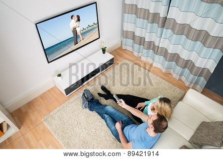 Couple Sitting In Front Television
