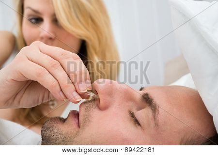 Woman Inserting Nose Clip Device Into Man Nose