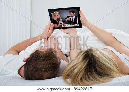 Couple With Digital Tablet In Bedroom
