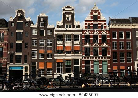 AMSTERDAM, NETHERLANDS - AUGUST 9, 2012: Bicycles parked in front of the traditional Dutch brick houses on Rokin Street in Amsterdam, Netherlands.