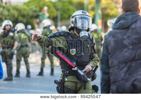 ATHENS, GREECE - APR 16, 2015: Riot police, take cover during a rally in front of the Athens University, which is under occupation by protesters leftist and anarchist groups.