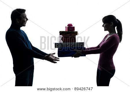 one  couple woman man offering christmas gifts in silhouette studio isolated on white background