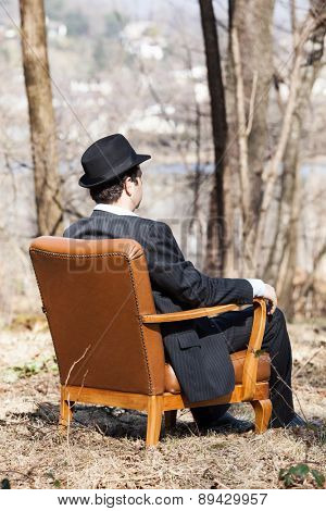 man alone in the woods sitting on a vintage armchair, rear view