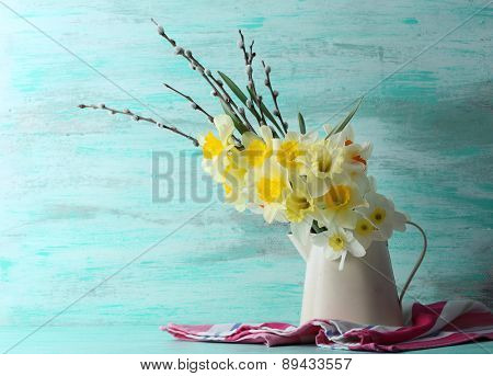 Fresh narcissus flowers with willow sprigs on color wooden background