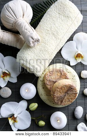 Still life with beautiful blooming orchid flower, spa treatment and pebbles, on wooden background