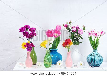 Beautiful composition with different flowers in vases on wall background