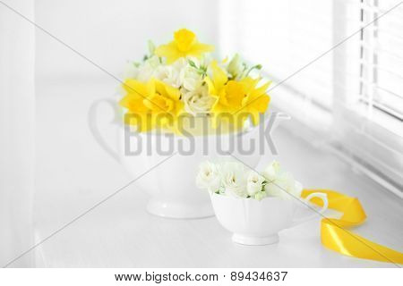 Beautiful bouquet of yellow daffodils and roses in teapot on windowsill