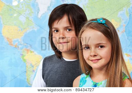 Children in geography class - portrait in front of large wall map, with copy space